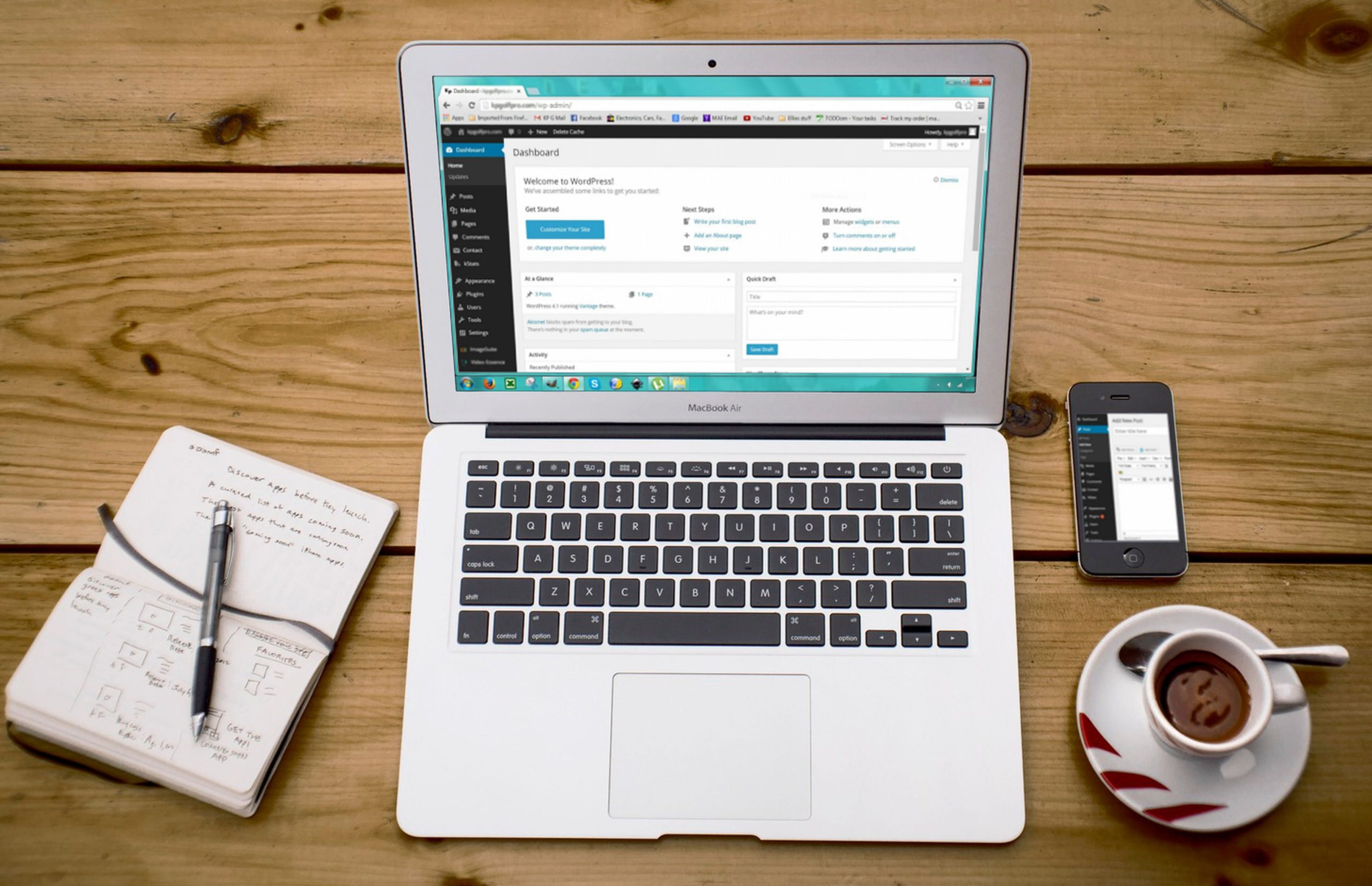 laptop showing WordPress sitting on table with a notebook